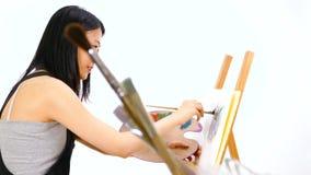 Het Aziatische kunstenaar schilderen bij schildersezel stock footage