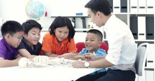 Het Aziatische leraar uitbreiden zich aan student in anatomieklasse met skeletmodel stock footage