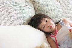 Het Aziatische leuke meisje voelt droevige speelarts met stethoscoop royalty-vrije stock foto