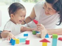 Het Aziatische mamma en meisjesjong geitje spelen met blokken Uitstekende gevolgen en Royalty-vrije Stock Afbeeldingen