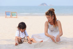 Het Aziatische mamma en zoons spelen op strand Royalty-vrije Stock Foto's