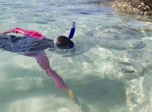 Het Aziatische meisje bereikt voor vissen terwijl het snorkelen Stock Afbeeldingen