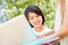 Het Aziatische meisje gebruikt een computer app royalty-vrije stock afbeeldingen