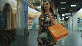 Het Aziatische meisje komt uit de opslag stock videobeelden