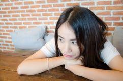 Het Aziatische meisje legt op houten lijst stock foto