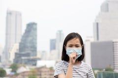 Het Aziatische meisje lijdt aan hoest met de bescherming van het gezichtsmasker, leuk kind die gezichtsmasker wegens luchtvervuil royalty-vrije stock afbeeldingen