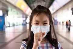 Het Aziatische meisje lijdt aan hoest met de bescherming van het gezichtsmasker, Ziek meisje royalty-vrije stock afbeelding