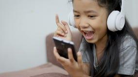 Het Aziatische meisje luistert aan de muziek door witte draadloze hoofdtelefoon met de duim van de gelukbespreking omhoog en beki stock video