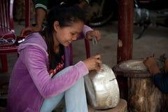 Het Aziatische meisje maakt een cijfer aangaande zilveren kom Stock Foto