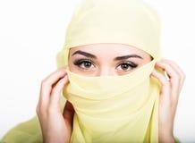 Het Aziatische meisje met bruine ogen die in een gele die sjaal stellen, muslimah modelleert in hijab op witte achtergrond wordt  Royalty-vrije Stock Foto's