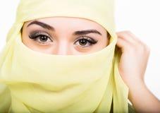 Het Aziatische meisje met bruine ogen die in een gele die sjaal stellen, muslimah modelleert in hijab op witte achtergrond wordt  Stock Afbeeldingen