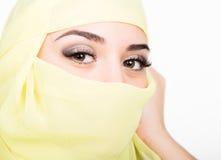 Het Aziatische meisje met bruine ogen die in een gele die sjaal stellen, muslimah modelleert in hijab op witte achtergrond wordt  Royalty-vrije Stock Fotografie