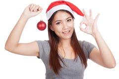 Het Aziatische meisje met rode de greepsnuisterij van de santahoed toont o.k. en glimlach Royalty-vrije Stock Foto