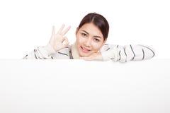 Het Aziatische meisje met sjaal toont O.K. rust haar kin op leeg teken Royalty-vrije Stock Afbeeldingen