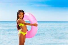Het Aziatische meisje met zwemt ring tegen exotisch zeegezicht stock afbeeldingen