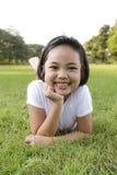 Het meisje ontspant en gelukkig glimlachend in het park Stock Afbeeldingen