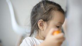 Het Aziatische meisje pelt rijpe sinaasappel voor thuis eet stock video