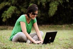 Het Aziatische meisje schrijft een e-mail openlucht royalty-vrije stock fotografie