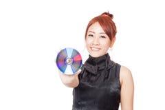 Het Aziatische meisje toont een schijf en een glimlach Stock Foto's