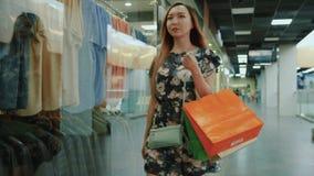 Het Aziatische meisje is winkelcentrum met het winkelen zakken stock footage