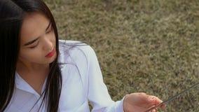 Het Aziatische meisje zit op gras en strijkt blad van een zwaard De persoon is ernstig stock video