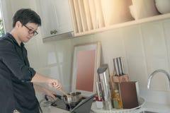 Het Aziatische mens koken met pot en gietlepel in keuken royalty-vrije stock afbeeldingen