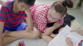 Het Aziatische moeder spelen met kinderen bij woonkamervloer stock footage