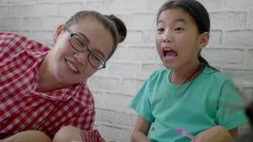 Het Aziatische moeder spelen met kinderen bij woonkamervloer stock videobeelden