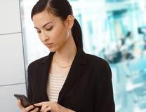 Het Aziatische onderneemster draaien op cellphone op kantoor stock foto's