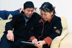 Het Aziatische oudere paar spelen met touchscreen tablet stock afbeelding
