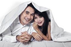 Het Aziatische paar verbergen onder deken Stock Afbeeldingen