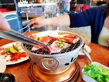 Het Aziatische ruwe gesneden rundvlees en het varkensvlees van de vrouwengrill op het hete roestvrij staalfornuis met rook royalty-vrije stock foto's