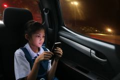 Het Aziatische studentenmeisje geniet van een telefoon op de persoonlijke auto's tijdens Th royalty-vrije stock foto