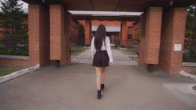 Het Aziatische studentenmeisje wandelt aan poorten en draaien rond en glimlacht gelukkig soms stock video