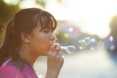 Het Aziatische tiener ontspannen met soepbel tegen mooi zonlicht royalty-vrije stock afbeeldingen