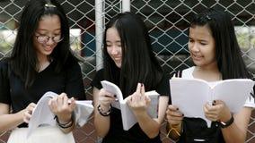 Het Aziatische tienerlezing boeken met gelukgezicht stock footage