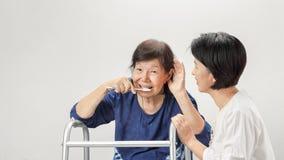 Het Aziatische verlies van het gehoor van de oudstenvrouw, Hard van hoorzitting stock afbeelding