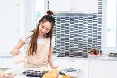 Het Aziatische vrouw gelukkig koken en het bakken cake in alleen keuken pe royalty-vrije stock afbeelding
