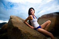 Het Aziatische vrouw ontspannen op de rots stock foto