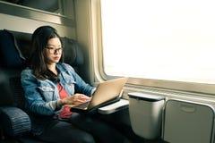 Het Aziatische vrouwenwerk aangaande laptop op trein, bedrijfsreisconcept, warme lichte toon Royalty-vrije Stock Fotografie