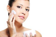 Het Aziatische wijfje van de schoonheid skincare van haar gezicht Stock Afbeeldingen