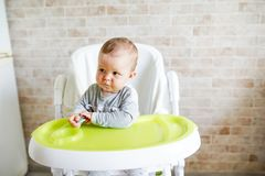 Het babykind eet voedsel zelf met lepel jong geitje als hoge voorzitter in zonnige keuken Achtergrond met exemplaarruimte royalty-vrije stock fotografie