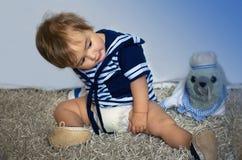 Het babymeisje in het zeevaart gestreepte vest zit op het tapijt stock foto