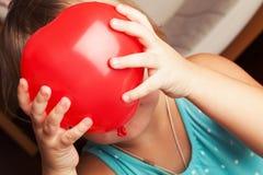 Het babymeisje houdt kleine rode hart gevormde ballon Stock Fotografie