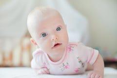 Het babymeisje kruipt op het witte bed Royalty-vrije Stock Afbeeldingen