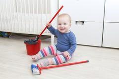 Het babymeisje 10 maanden doet thuis het schoonmaken Stock Foto's
