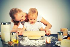 Het babymeisje met haar moederkok, bakt Stock Fotografie