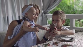 Het babymeisje probeert om glas met roomijs te grijpen stock videobeelden