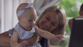 Het babymeisje probeert om het scherm van laptop te grijpen stock footage