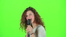 Het babymeisje zingt in retro microfoon vurige liederen Het groene scherm stock videobeelden